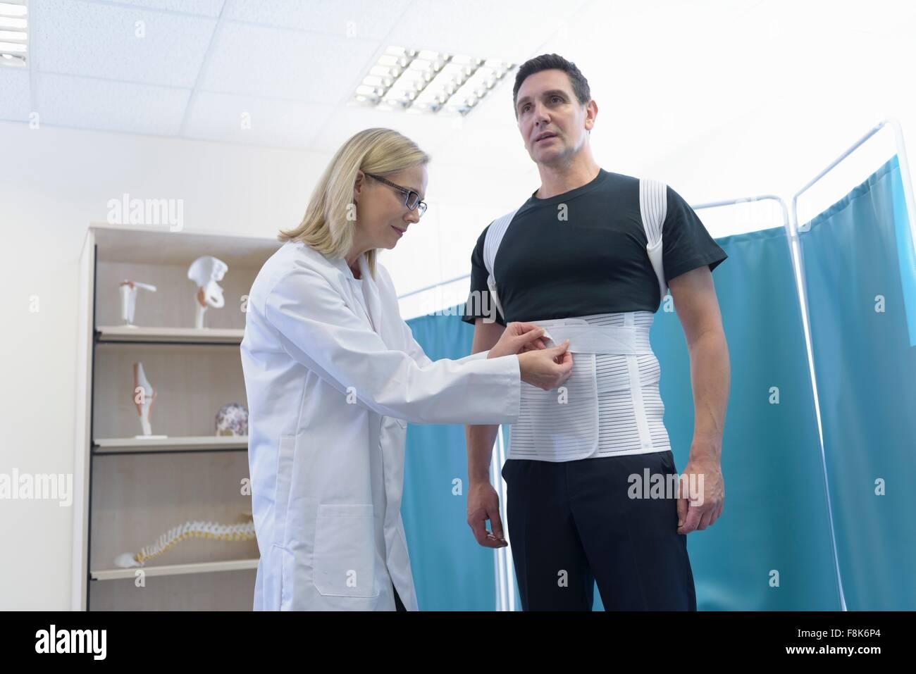 Arzt passt orthopädische Unterstützung für Patienten Stockbild