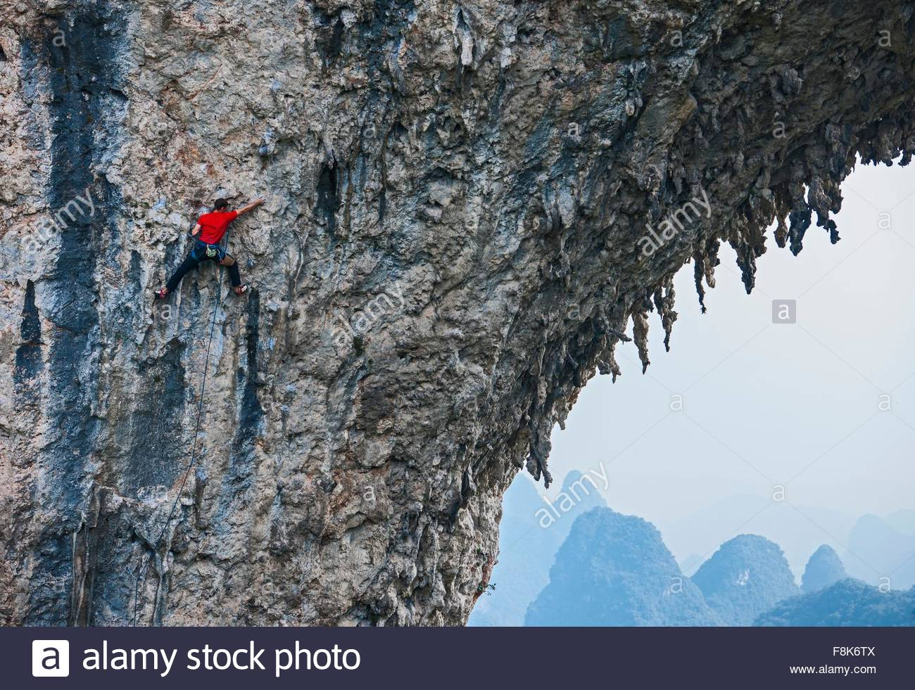 Männliche Kletterer Klettern auf Moon Hill - ein Kalksteinfelsen in Yangshuo, Guangxi Zhuang, China Stockbild
