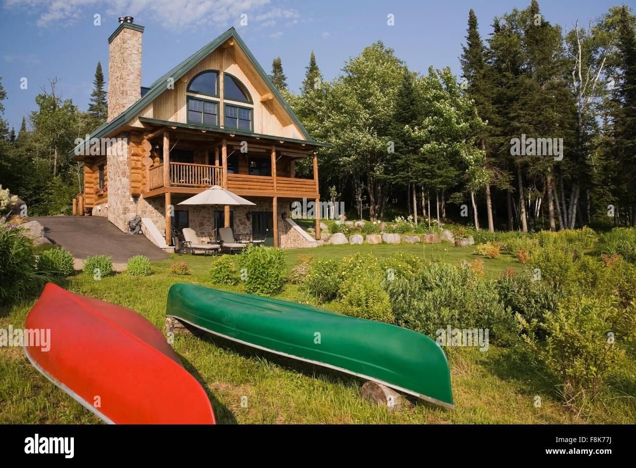 Handgefertigte Fichte Blockhaus Mit Feldsteinen Kamin Und Grün Metalldach  Im Sommer, Quebec, Kanada