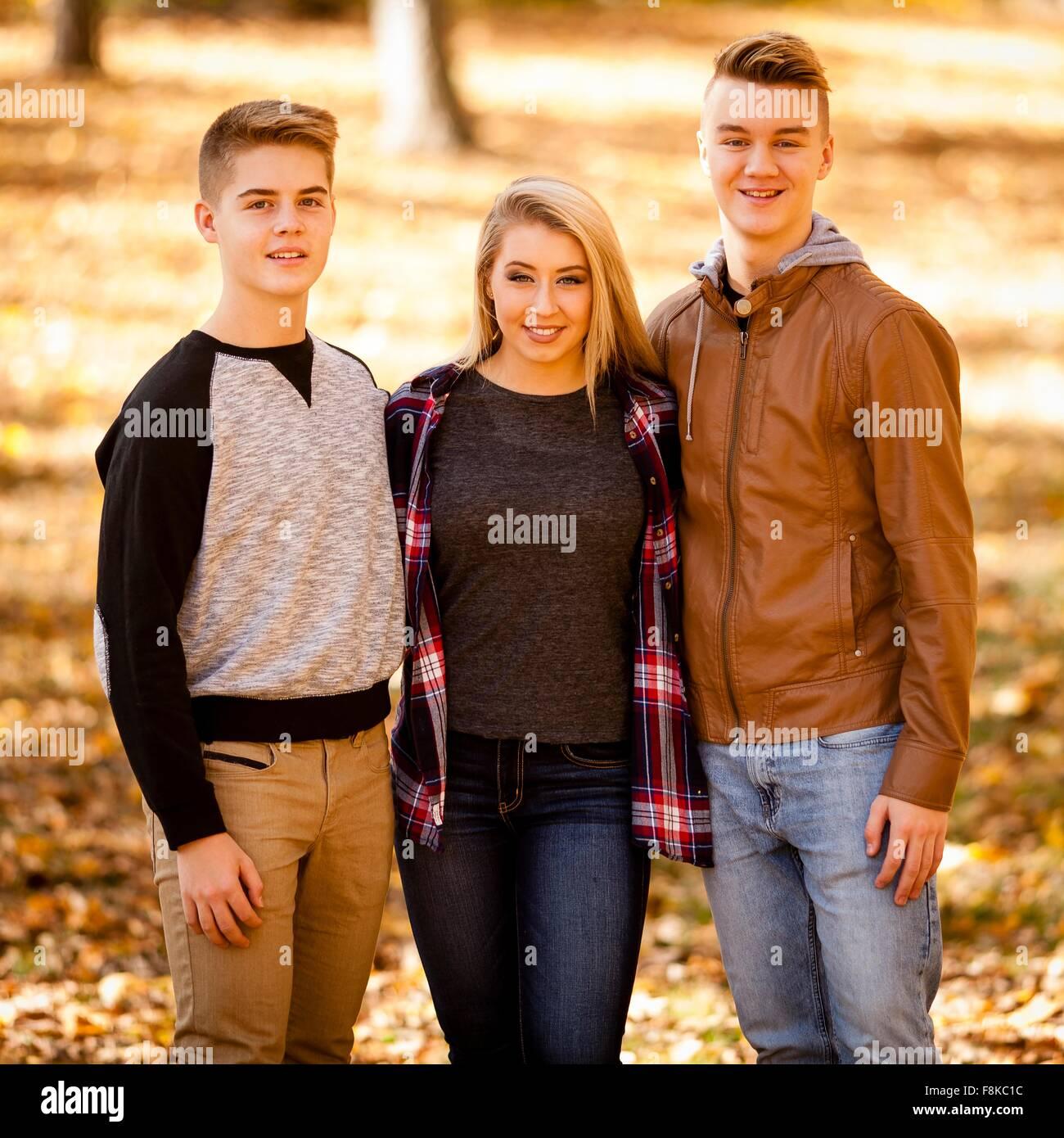Porträt der jungen Frau und zwei Teenager-Brüder im herbstlichen Wald Stockfoto
