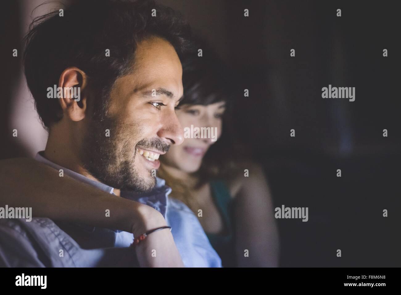 Seitenansicht der jungen Paare, Kopf und Schultern von Laptop Computer Bildschirm lächelnd beleuchtet Stockbild