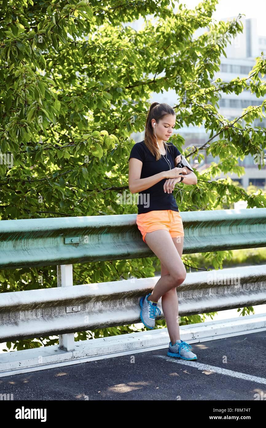 Junge weibliche Läufer Smartwatch überprüfen Stockbild