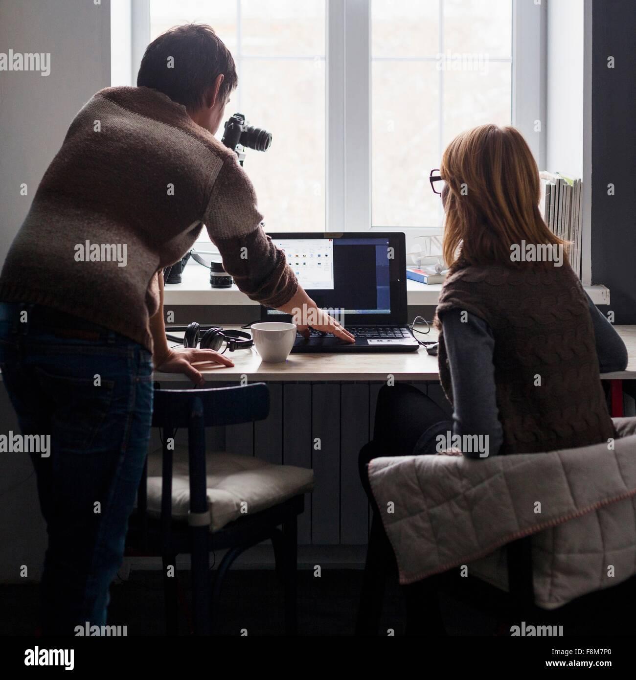 Mitte erwachsenen Mann und Frau mit Laptop am Schreibtisch Rückansicht Stockbild