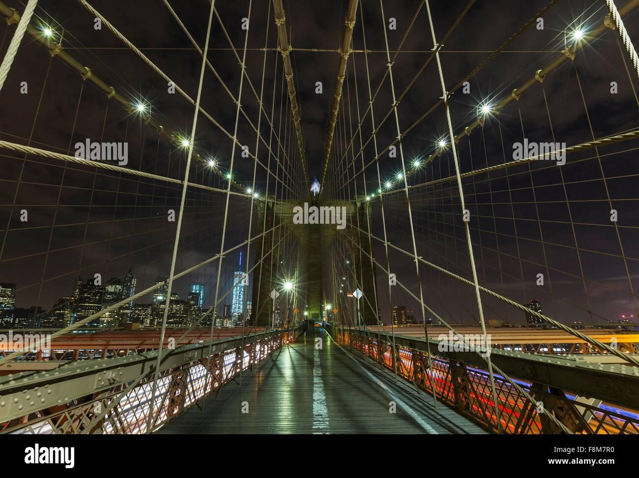 Brooklyn Brücke Gehweg und fernen Finanzviertel Skyline von Manhattan in der Nacht, New York, USA Stockbild