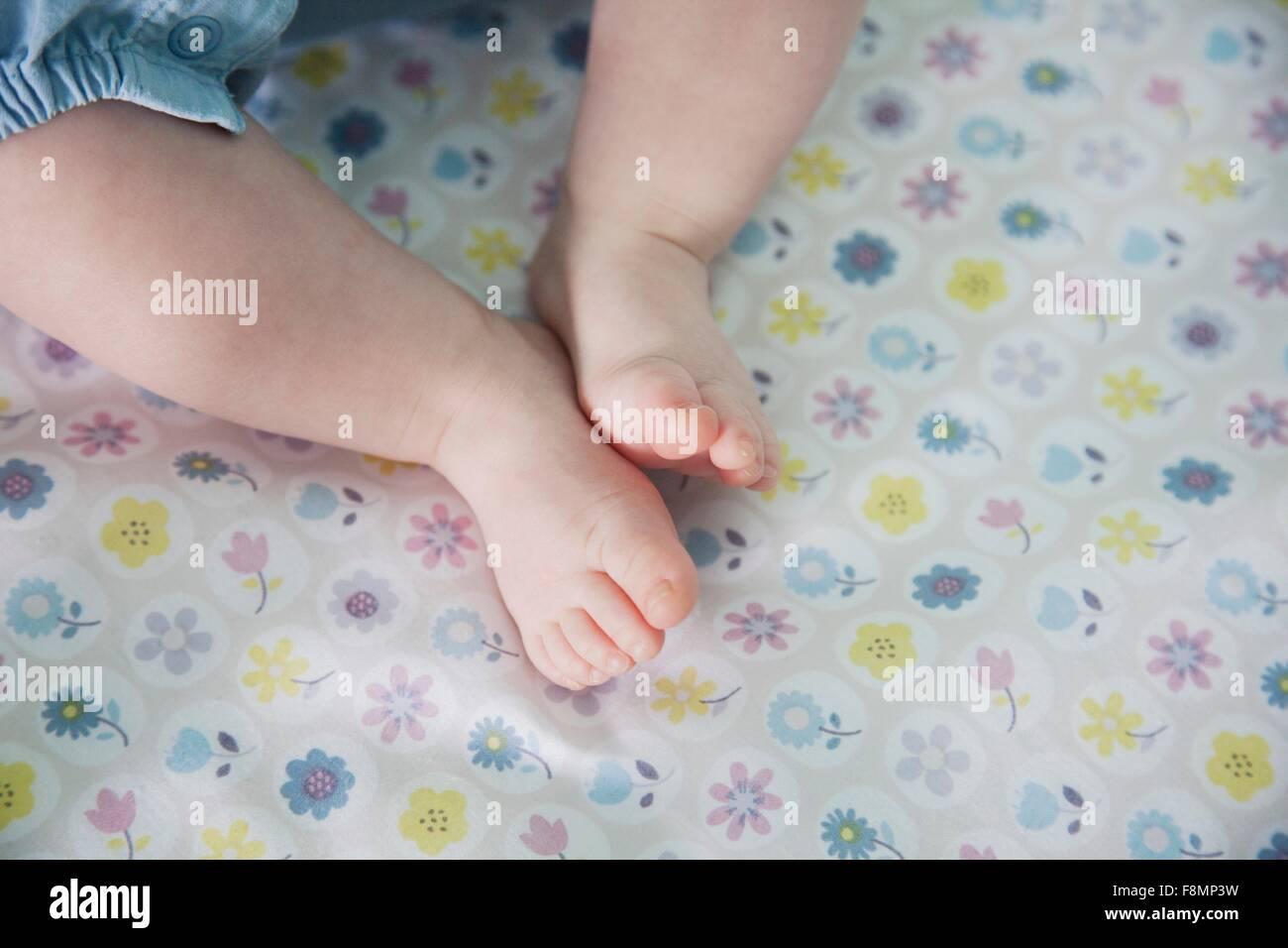 Baby Mädchen hinlegen, Füße im Fokus Stockbild