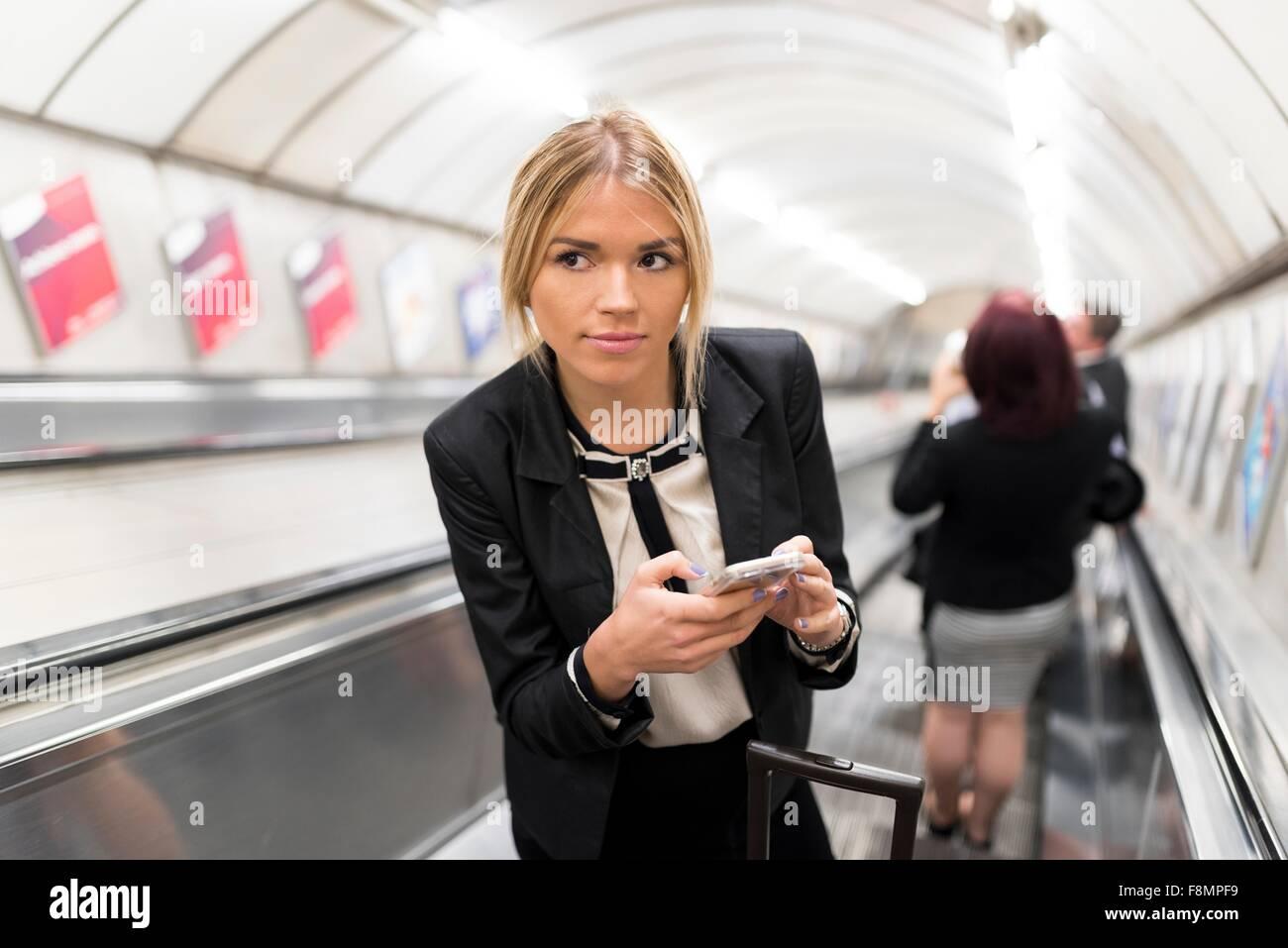 Geschäftsfrau SMS auf Rolltreppe, London Underground, UK Stockbild