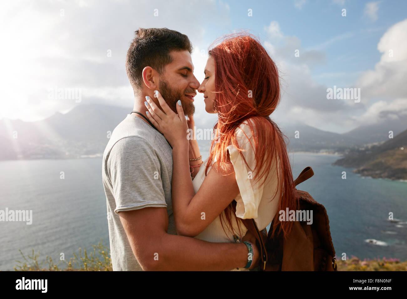 Porträt des jungen Mann und Frau zu einen romantischen Kuss zu teilen. Liebevolle junge Paar genießen Stockbild
