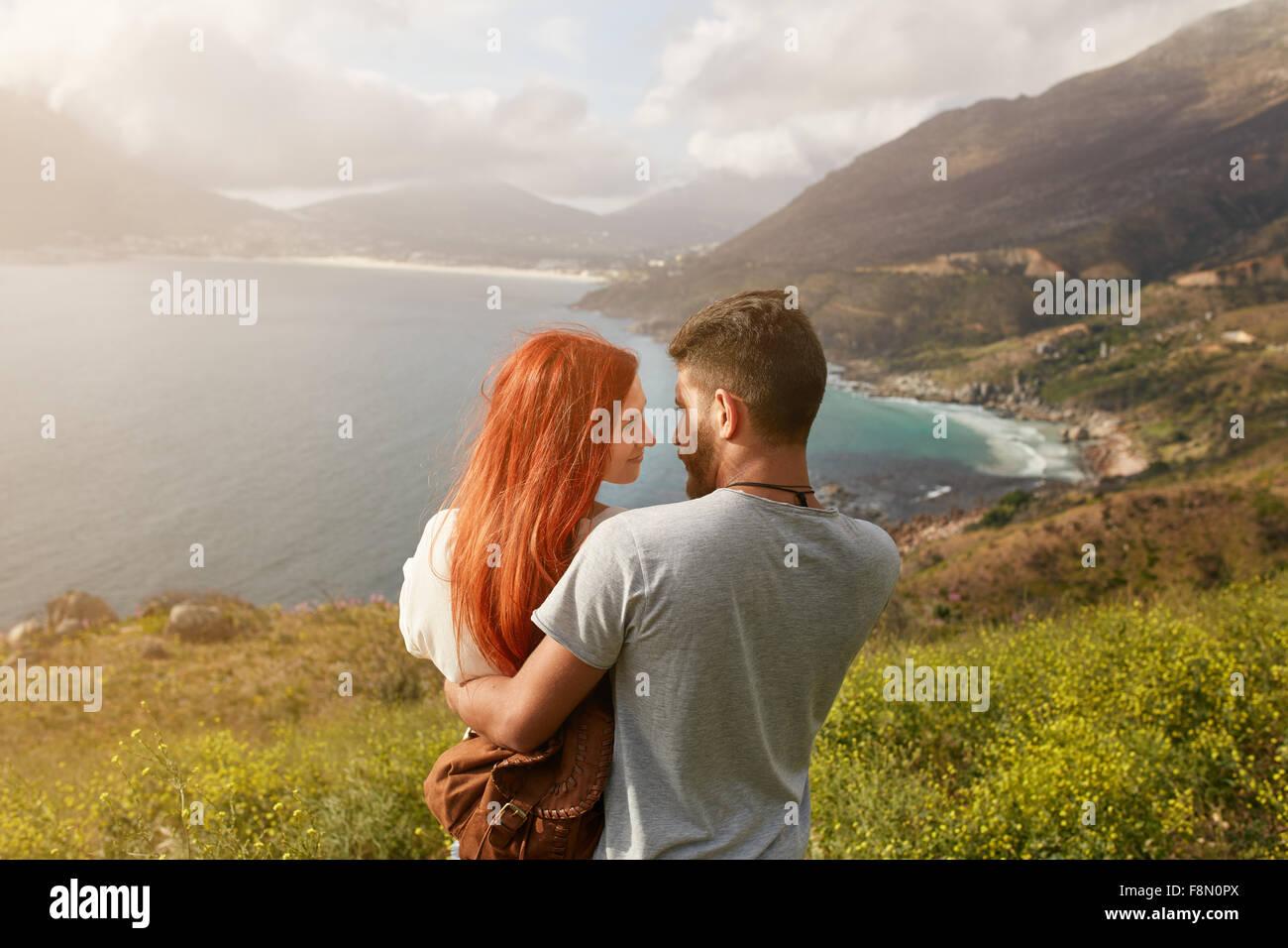 Romantische junges Paar umarmt und sahen einander an einem sonnigen Tag im Freien. Mann und Frau, die in jedem anderen Stockbild