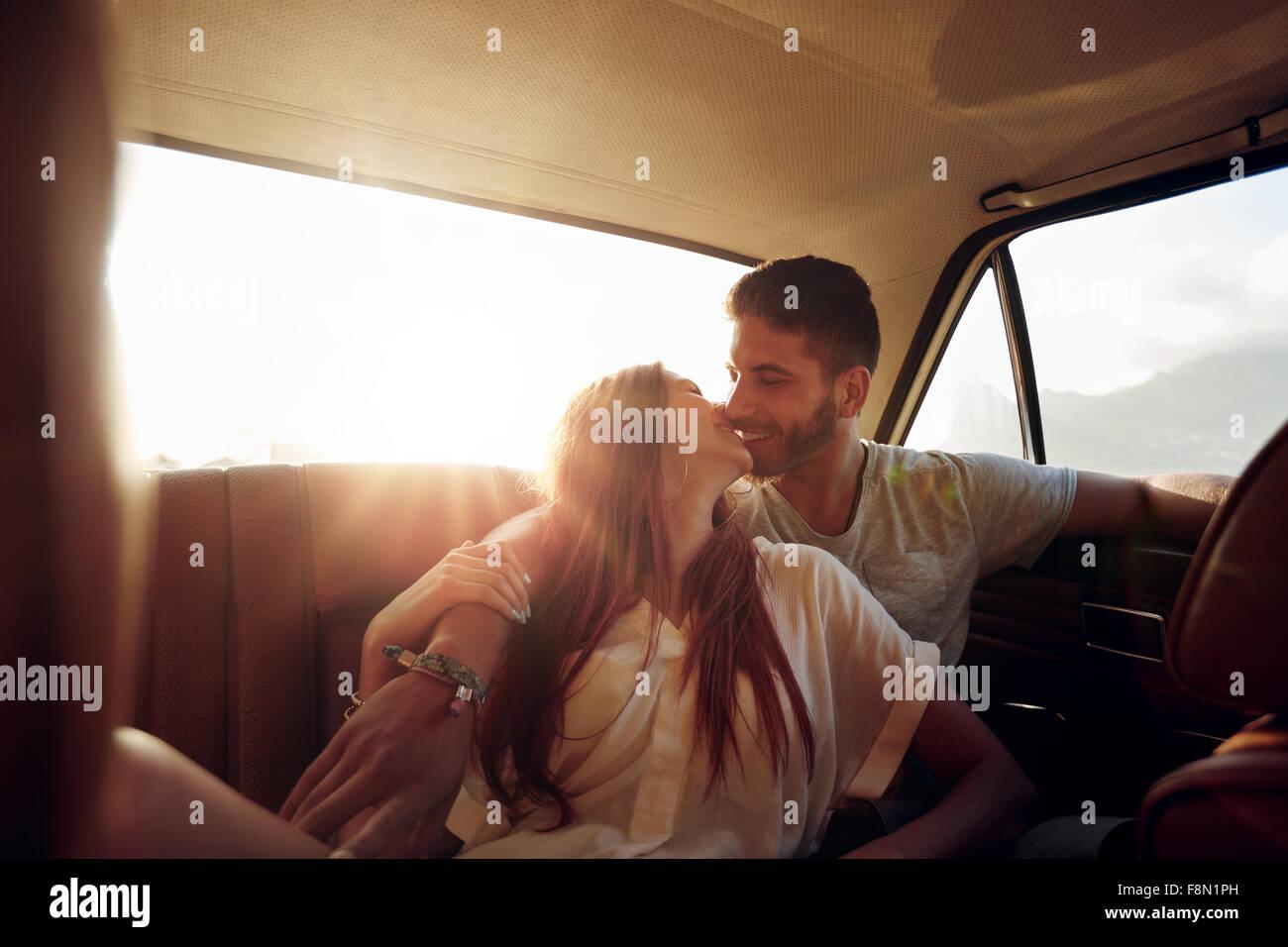 Zärtlich junges Paar sitzt im hinteren Sitz eines Autos. Junger Mann und Frau im Rücksitz eines Fahrzeugs Stockbild