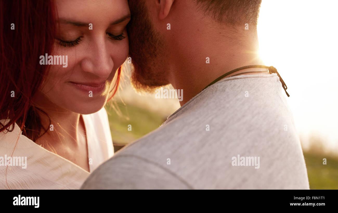 Schuss von zärtliche junge Frau umarmt ihr Freund mit geschlossenen Augen hautnah. Romantische Pärchen Stockbild