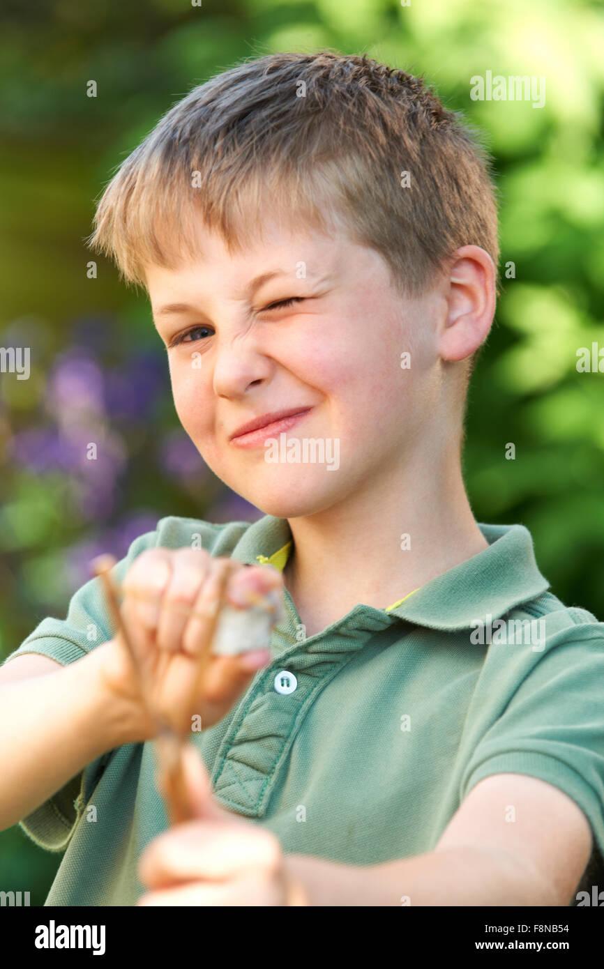 Junge mit dem Ziel Schleuder im Garten Stockbild