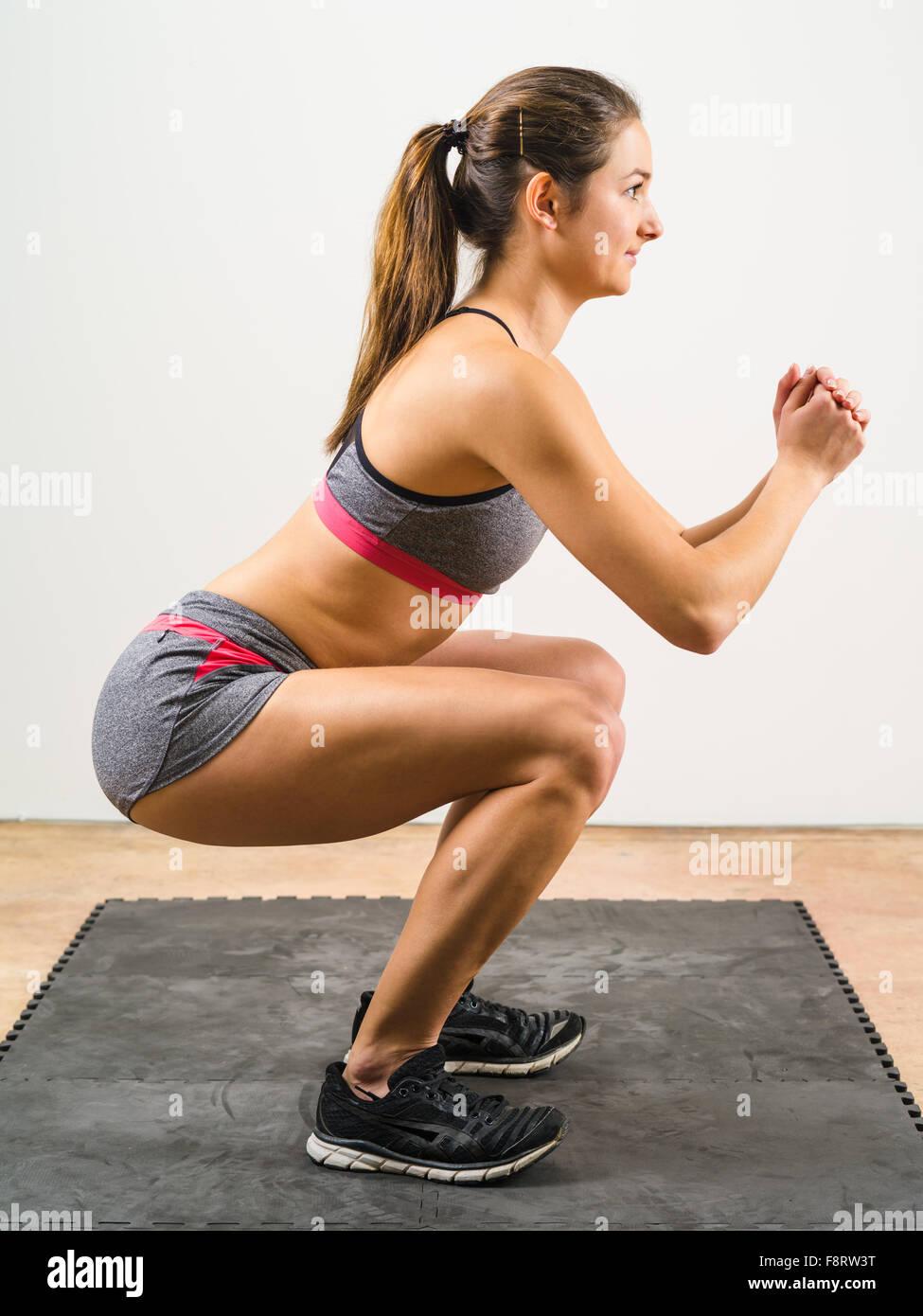 Foto einer jungen Frau trainieren und dabei eine isometrische hocken auf einer schwarzen Bodenmatte. Stockbild