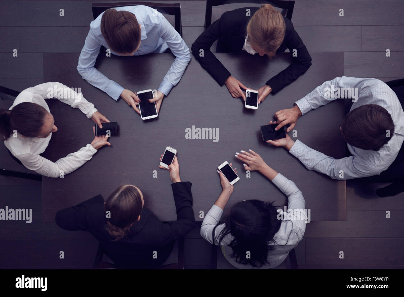 Geschäftsleute mit Smartphones sitzen um den Tisch, Ansicht von oben Stockbild