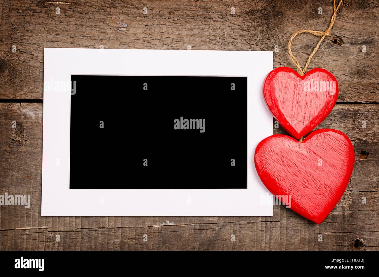 Zwei rote Herz aus Holz Formen mit einem leeren Bilderrahmen auf ...