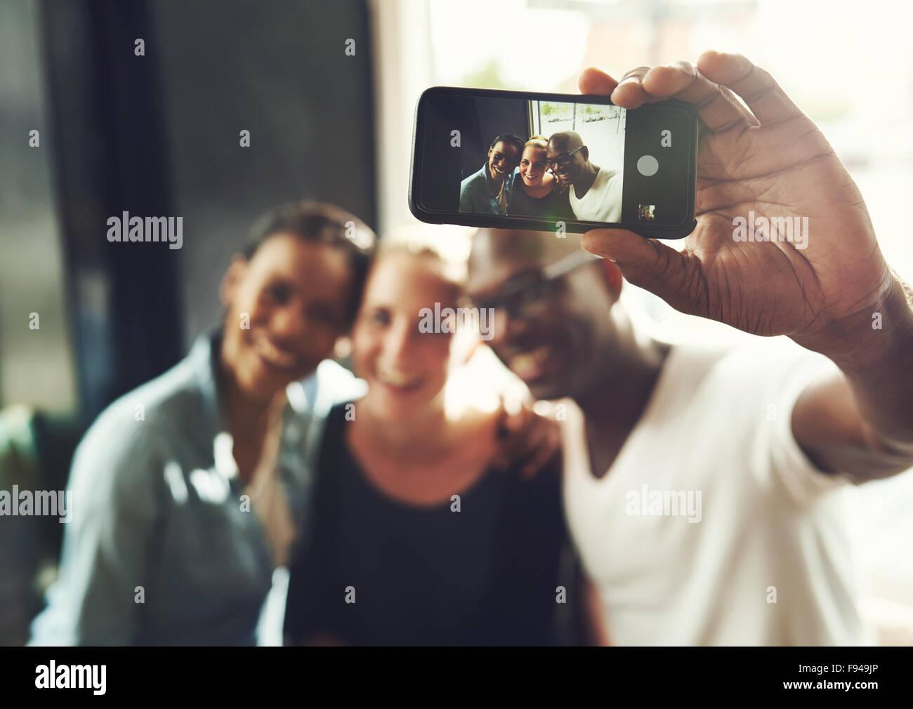 Multi ethnischen Freunde nehmen eine Selfie mit einem Telefon Stockbild