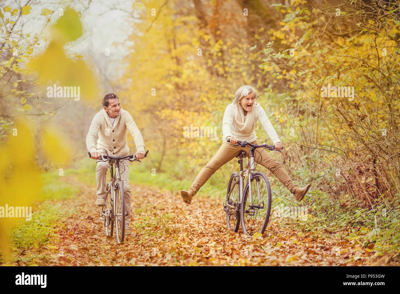 Aktive Senioren mit Fahrrad in der herbstlichen Natur. Sie haben Spaß im Freien. Stockbild