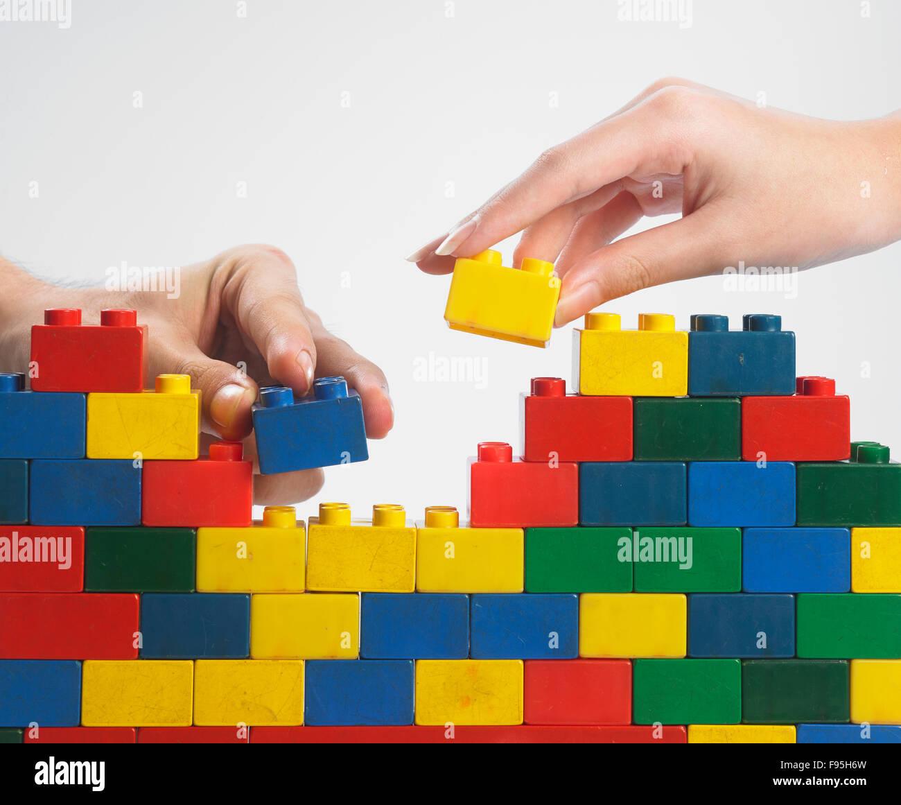 zwei hände teamarbeit stack-up lego set als wand auf weißem