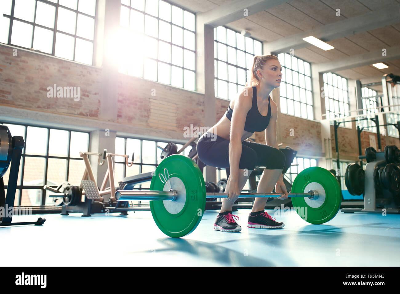 Entschlossen und stark Fitness Frau training mit schweren Gewichten im Fitnessclub. Kaukasische Sportlerin tun Gewichtheben Stockbild