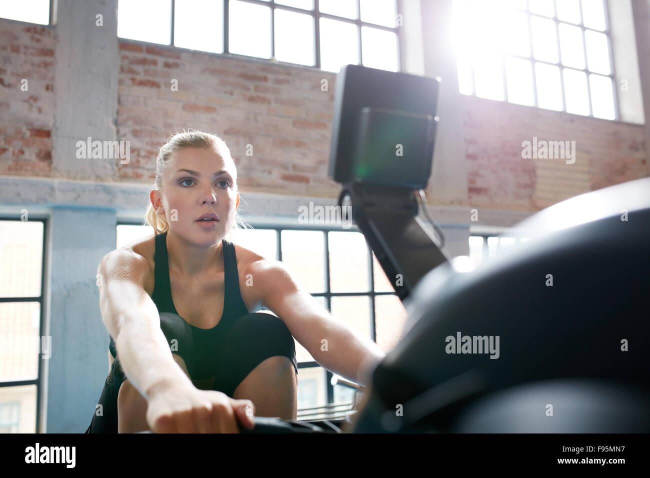 Passen Sie die junge Frau auf einem Rudergerät im Fitnessstudio trainieren. Kaukasischen Frauen tun, Cardio Stockbild