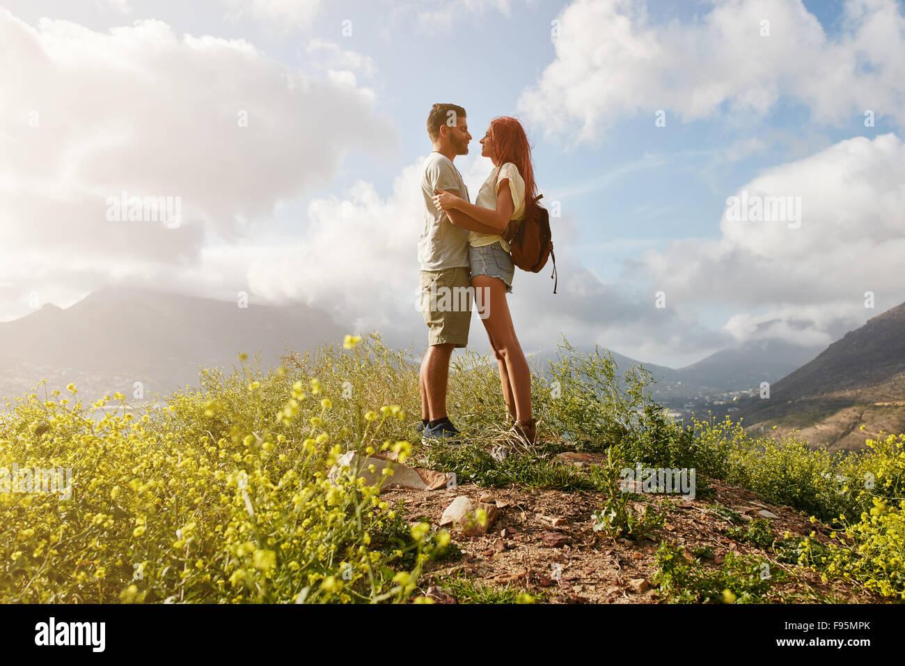 Porträt von verliebten Paar in Umarmung stehend auf einem Hügel. Junger Mann und Frau in der Liebe stehen Stockbild