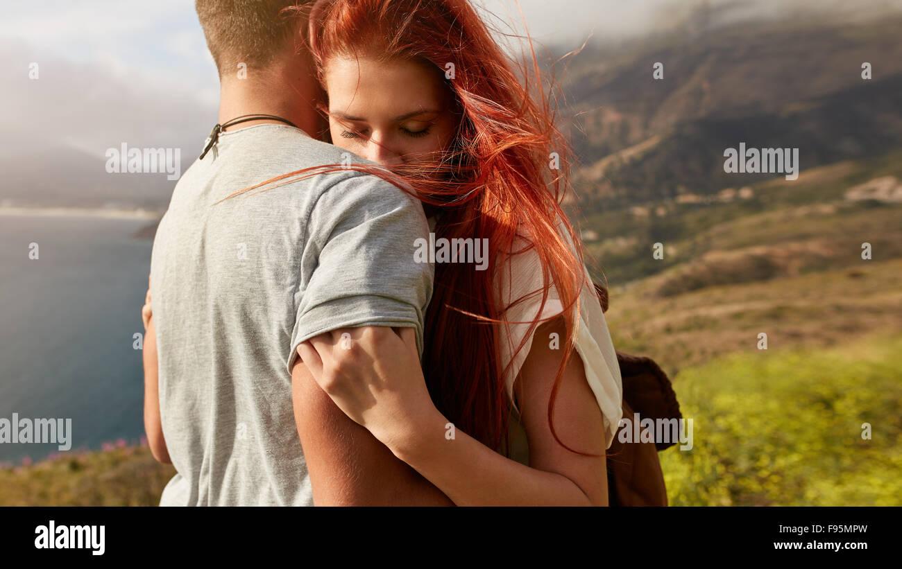 Schuss von junge Frau ihrem Freund umarmt hautnah. Junges Paar in Liebe umarmen im Freien. Stockbild