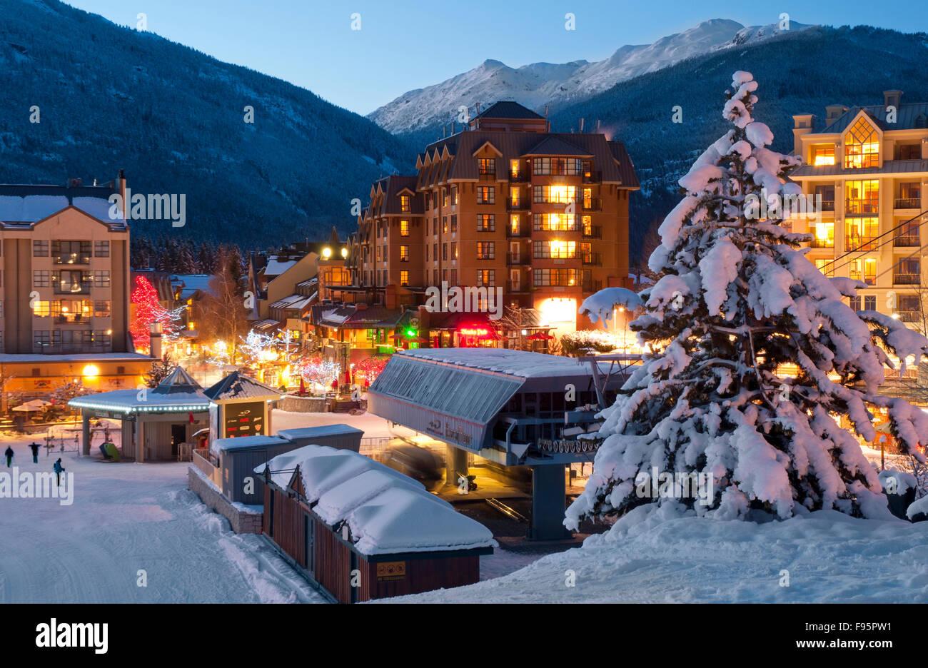 Whistler Village leuchtet mit Lichtern bei Sonnenuntergang an einem Winterabend Stockbild