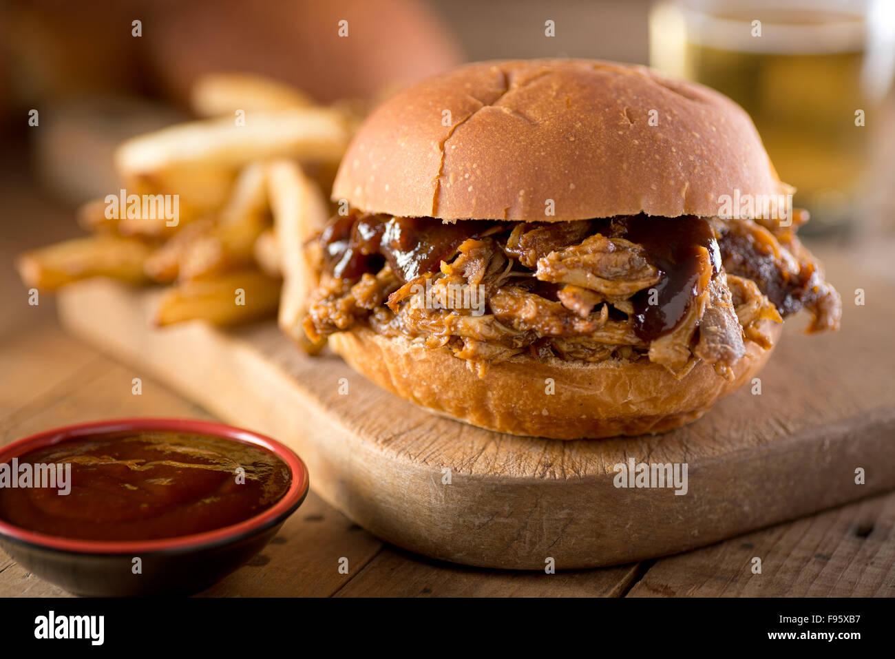 Eine köstliche gezogener Schweinesandwich mit Barbecue-Sauce auf einem Brötchen. Stockbild