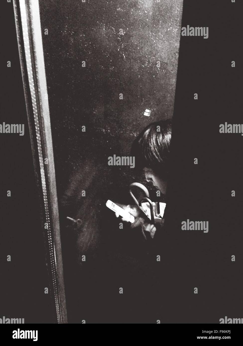 Mann mit Smartphone gesehen durch Fenster Stockbild