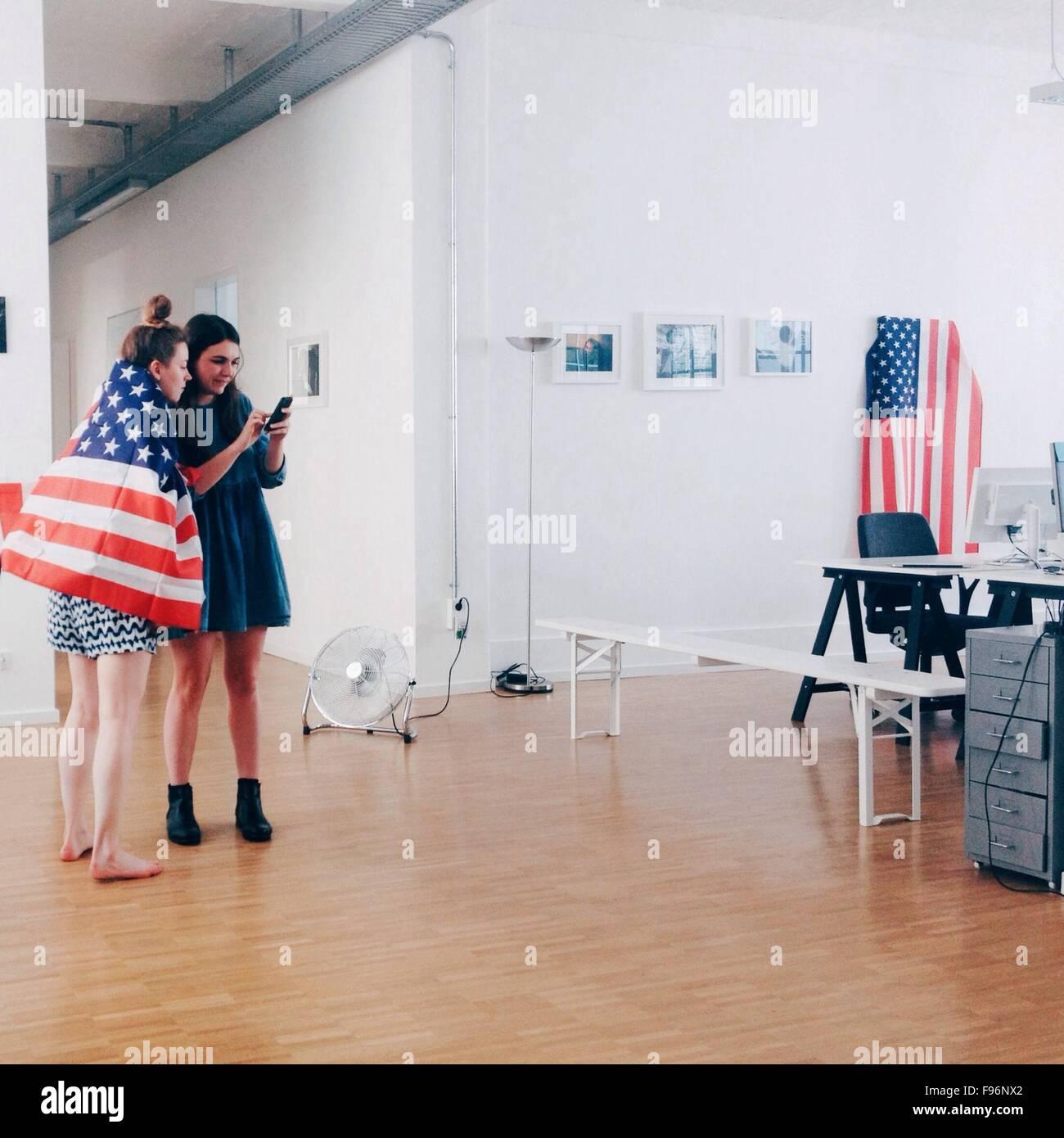 Voller Länge von jungen Frauen mit amerikanischen Flagge mit Handy im Büro Stockbild