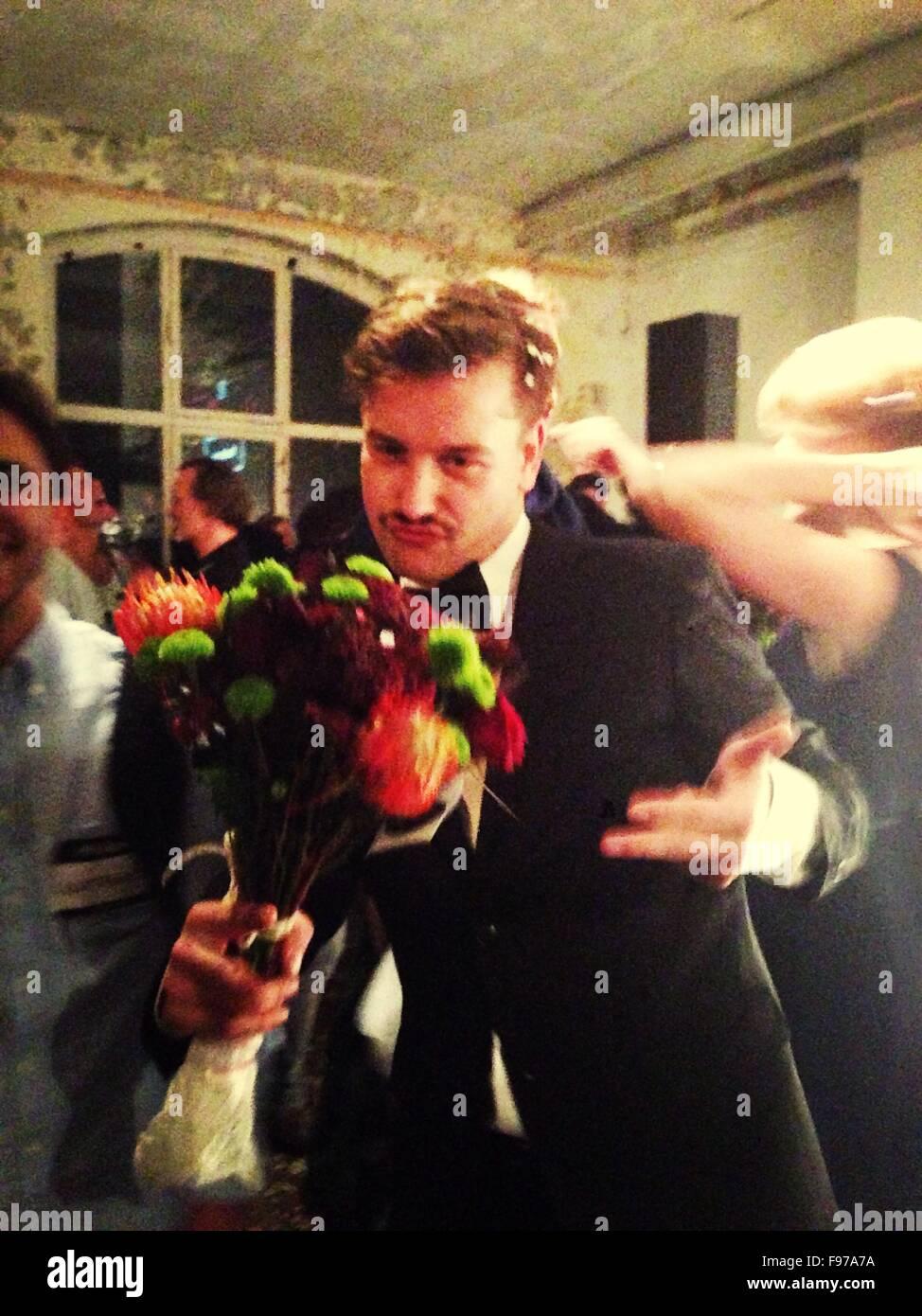 Junger Mann im Anzug Kräuseln der Lippen bei Veranstaltung mit gedrückter Bouquet Stockbild