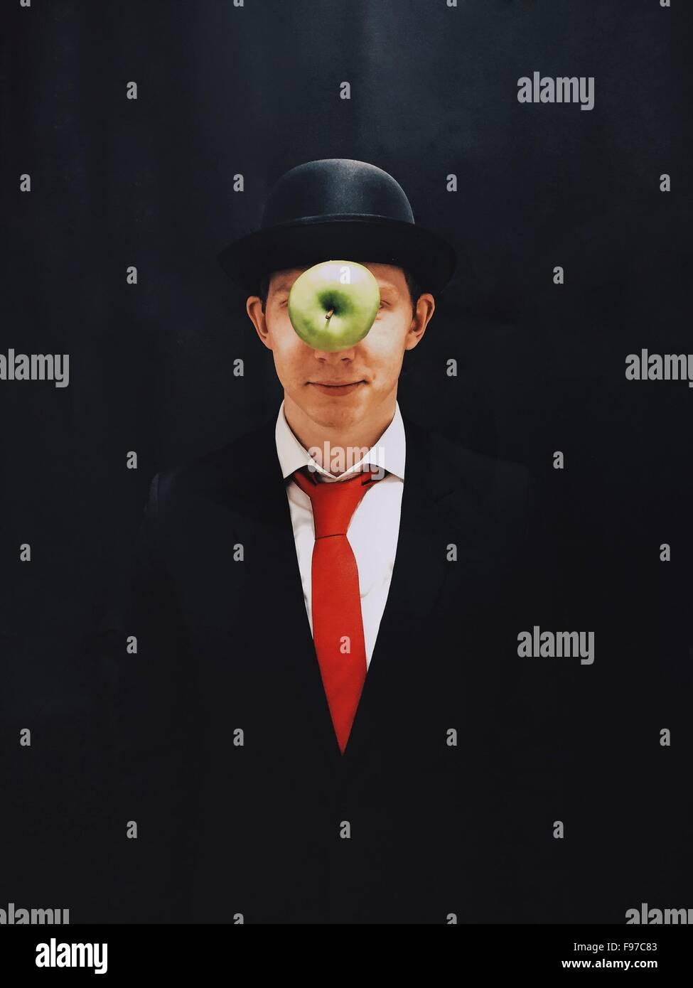 Apple In der Luft vor Mann mit Hut vor schwarzem Hintergrund Stockbild