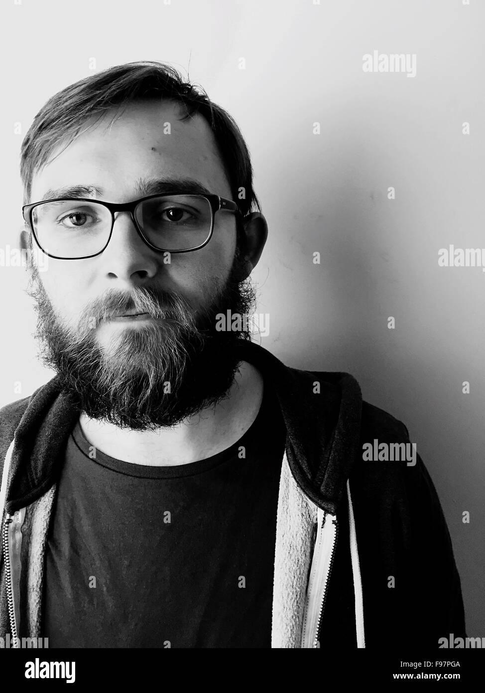 Porträt des Mannes mit Brille stehen gegen die Wand zu Hause Stockbild