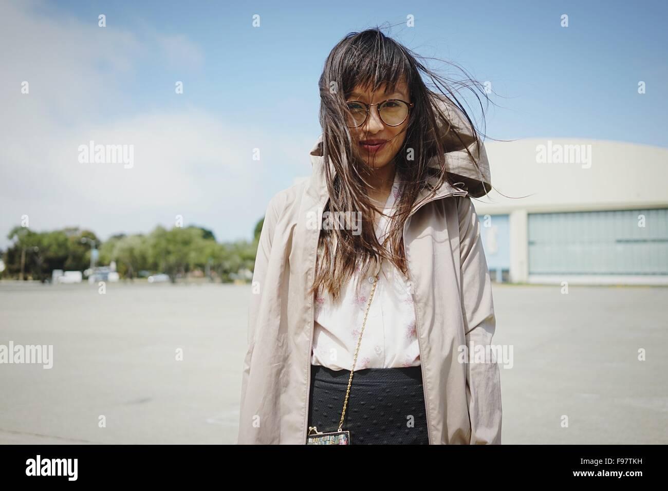Porträt der Frau, die durch Gebäude gegen Himmel Stockbild