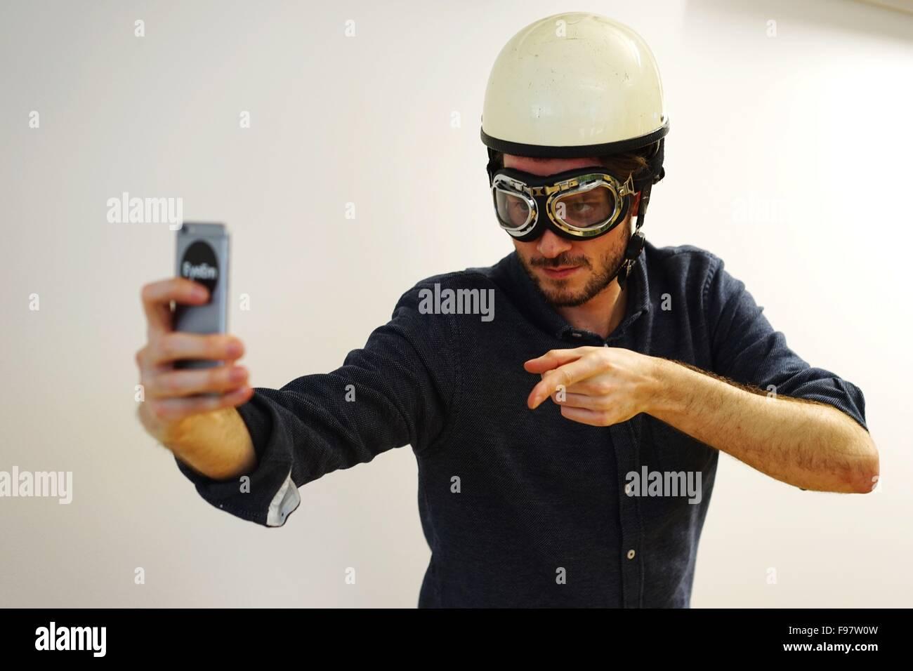 Junger Mann In Aviator Brille und Helm nehmen Selfie gegen weiße Wand Stockbild