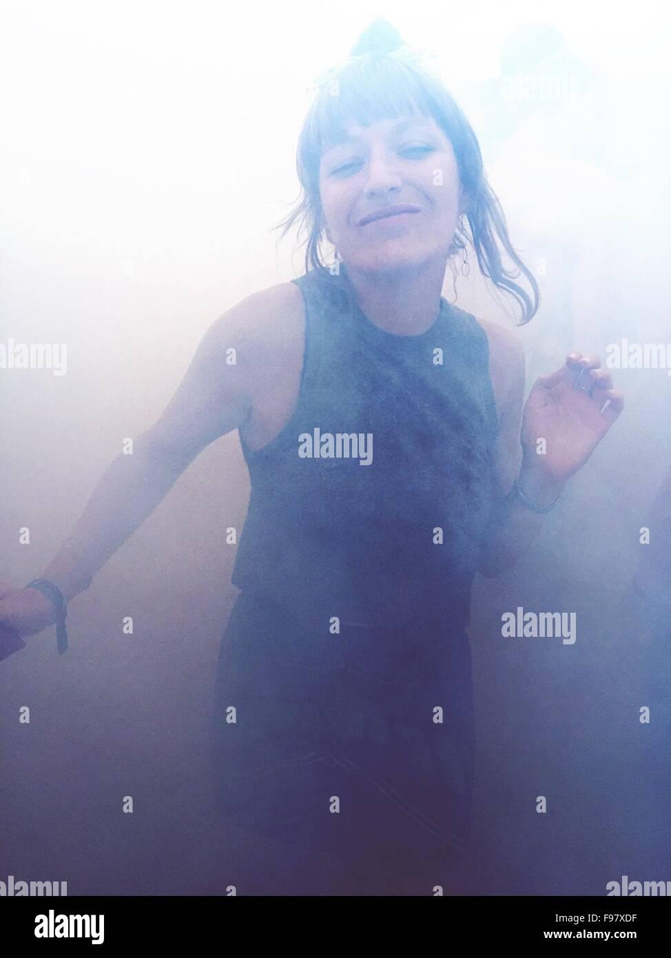 Porträt von glücklich Frau tanzt im Rauch Stockbild