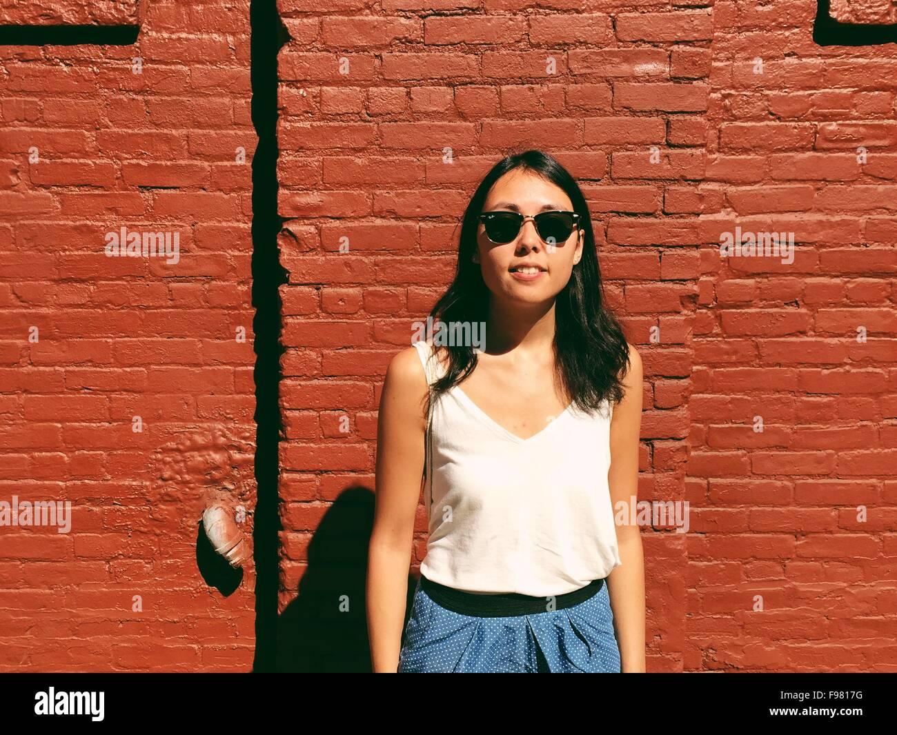 Porträt der schönen jungen Frau stehend gegen die roten Backsteinmauer Stockbild