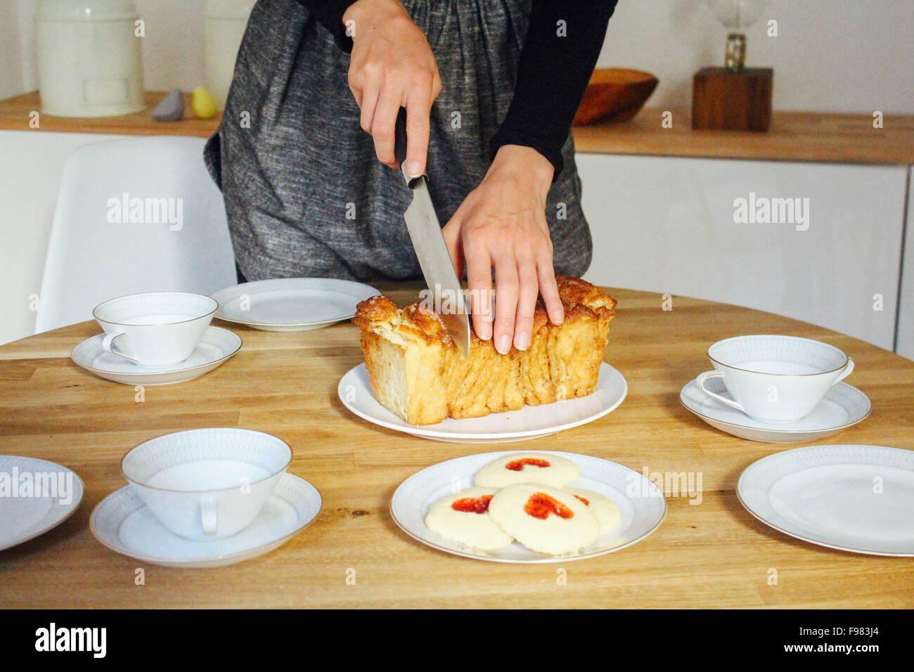 Frau Schneiden von Brot auf Tisch Stockbild