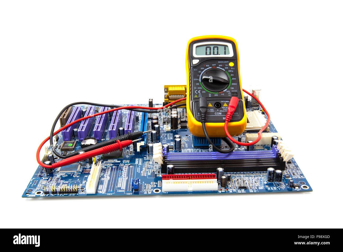Multimeter und Computer Platine auf weißem Hintergrund Stockbild