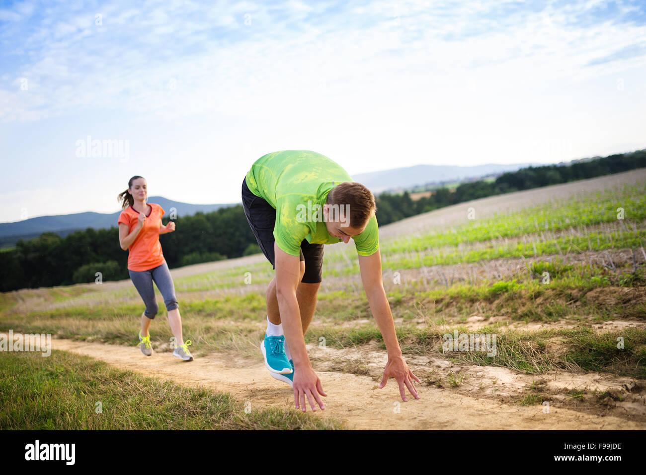 Männliche Läufer stolpern und fallen nach unten auf die Langlaufloipe Stockbild