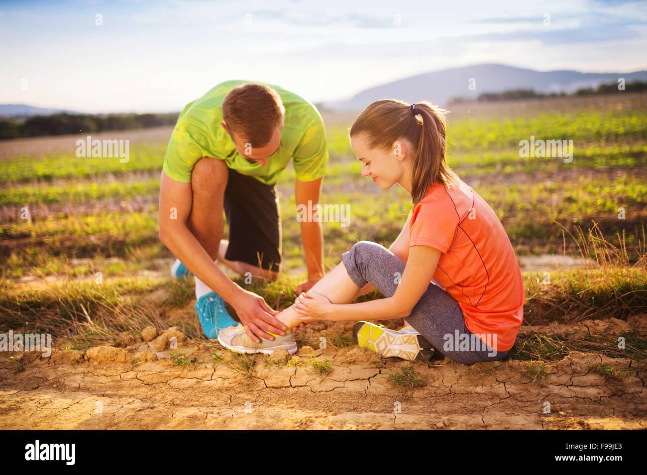 Verletzungen - Sport Frau mit verdrehten verstauchten Hilfe bekommen von Mann berühren ihren Knöchel. Stockfoto