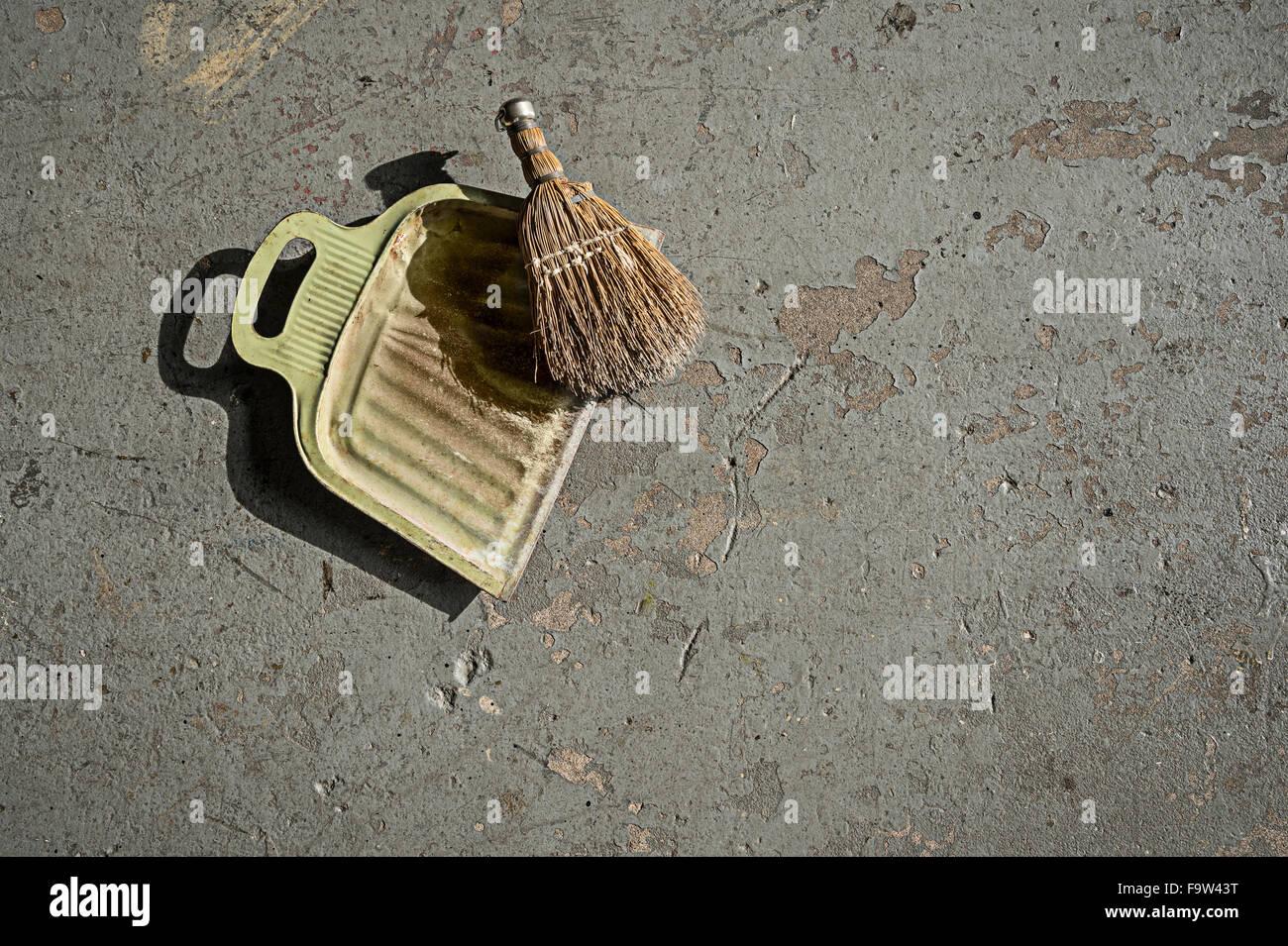 Kehrschaufel und Pinsel auf Zement-Boden Stockbild