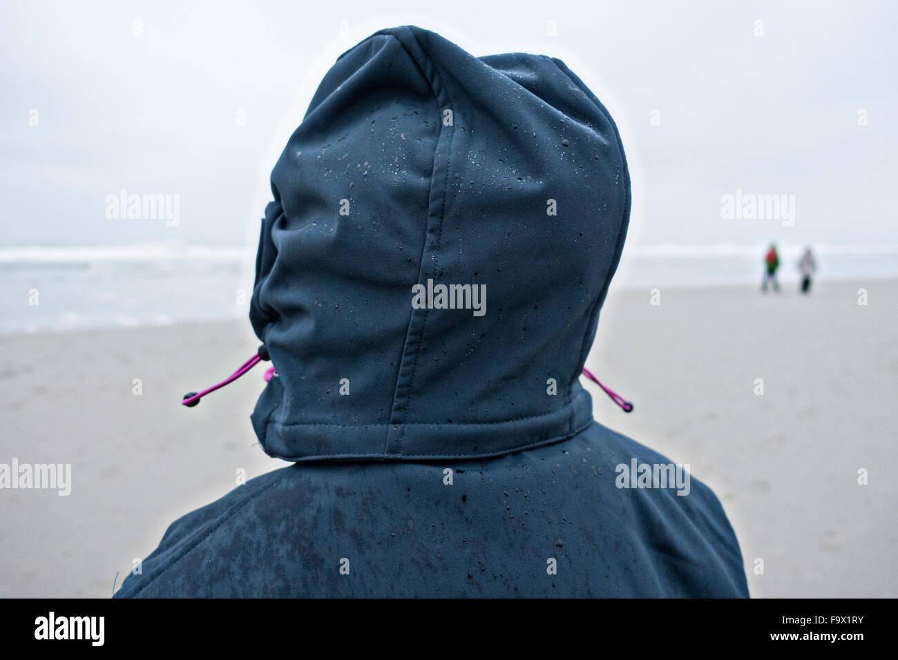 Deutschland, Insel Langeoog, Person mit nassen Kapuze am Strand Stockbild