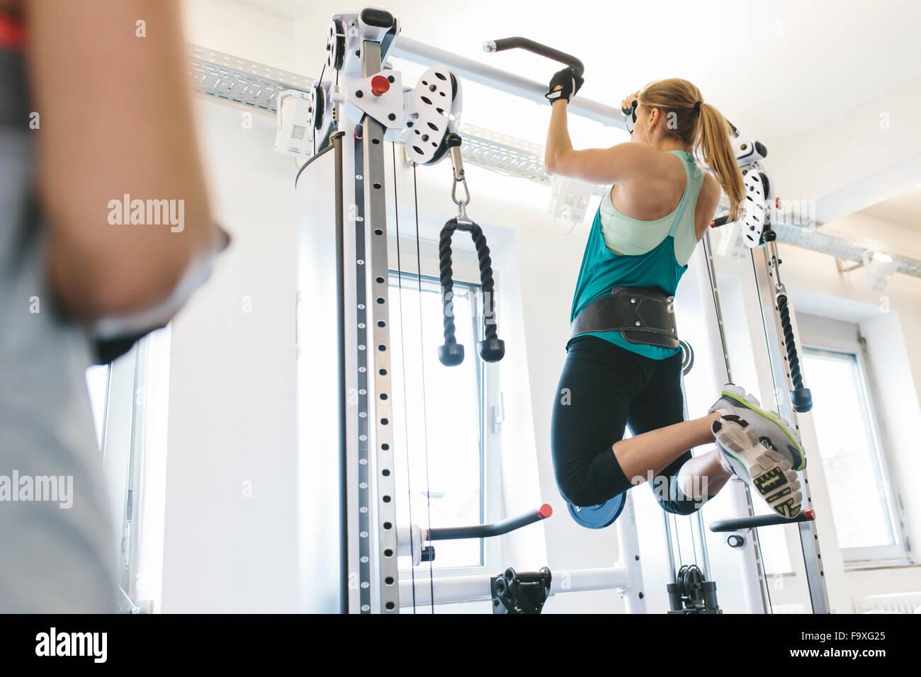 Frau macht Klimmzüge mit Gewichten im Fitnessstudio Stockbild