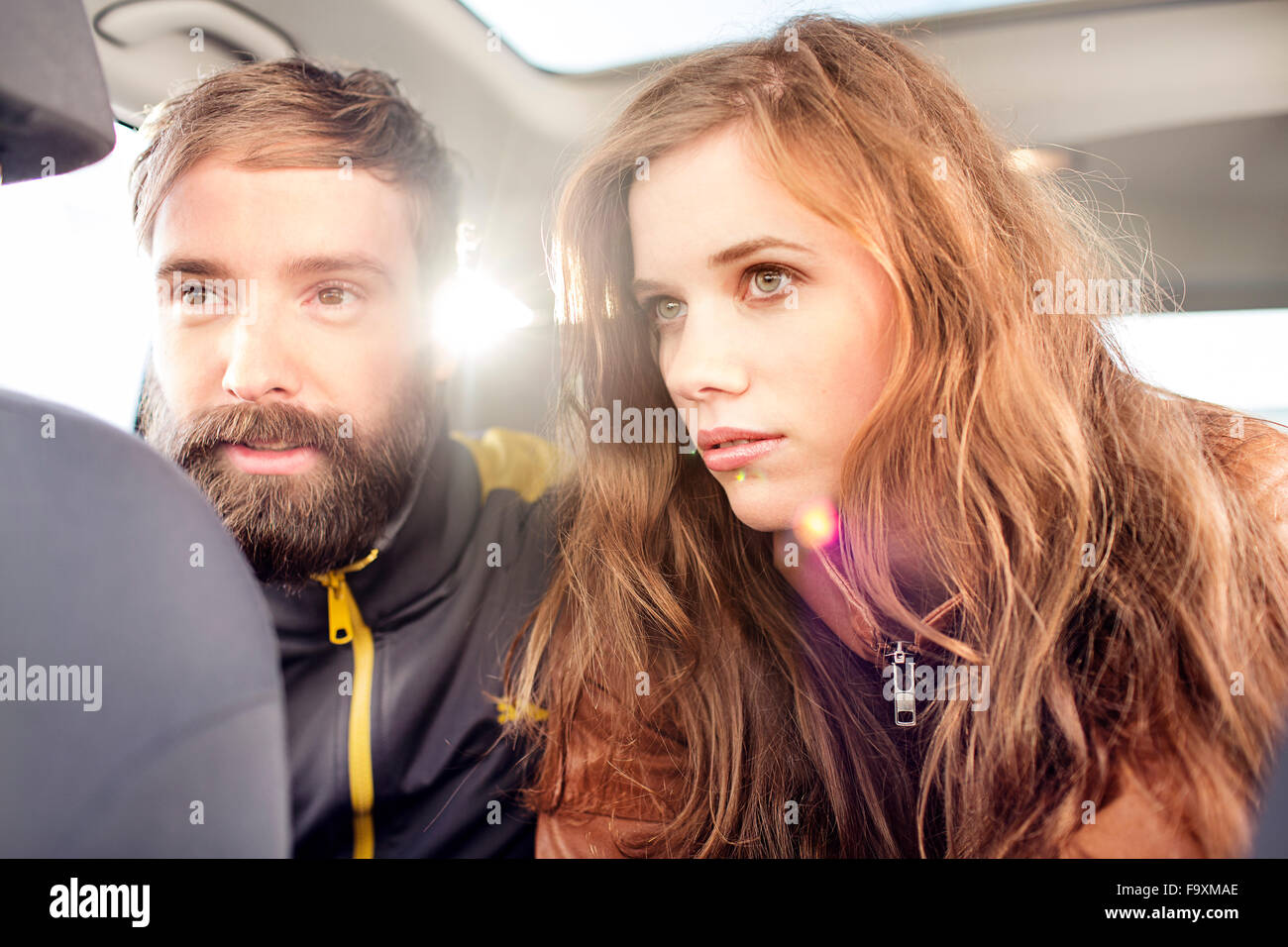 Paar auf dem Rücksitz eines Autos bei Gegenlicht Stockbild