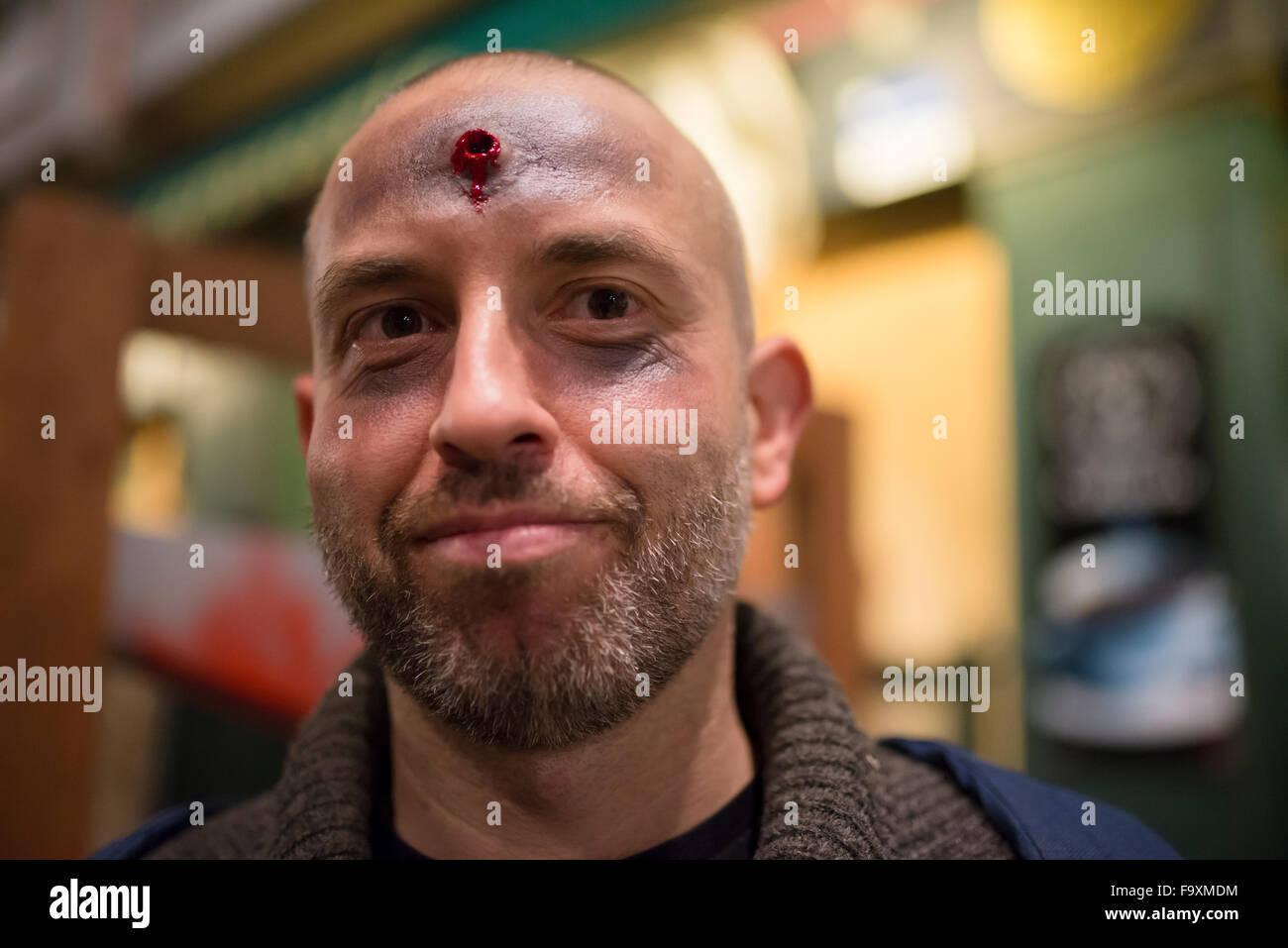 Bärtiger Mann mit gefälschten Schuss in seiner Stirn an Halloween Stockbild