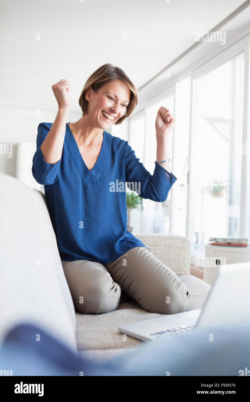 Glückliche Frau zu Hause shopping online- Stockbild