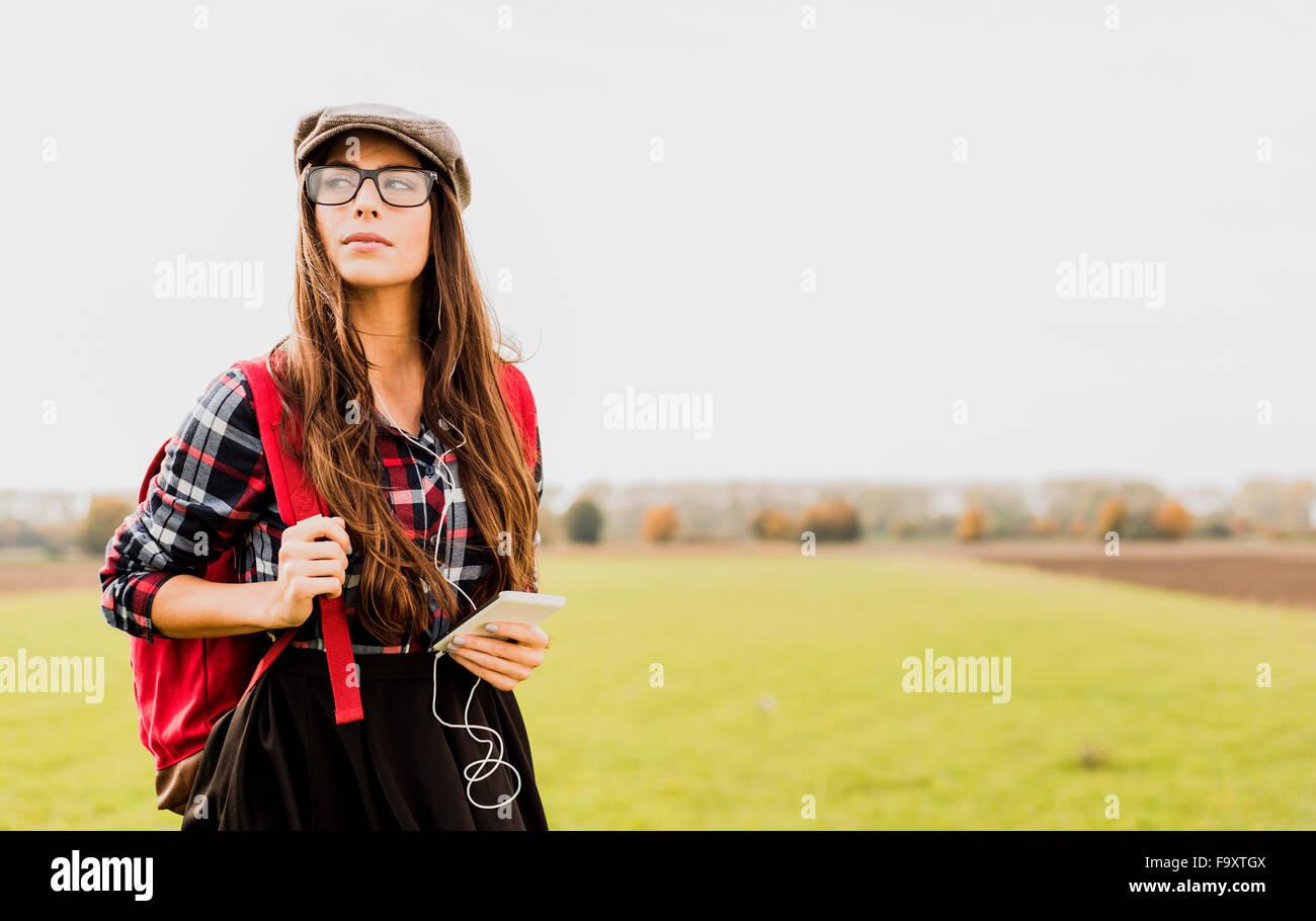 Junge Frau mit Rucksack und tragbares Gerät auf dem Lande Stockbild