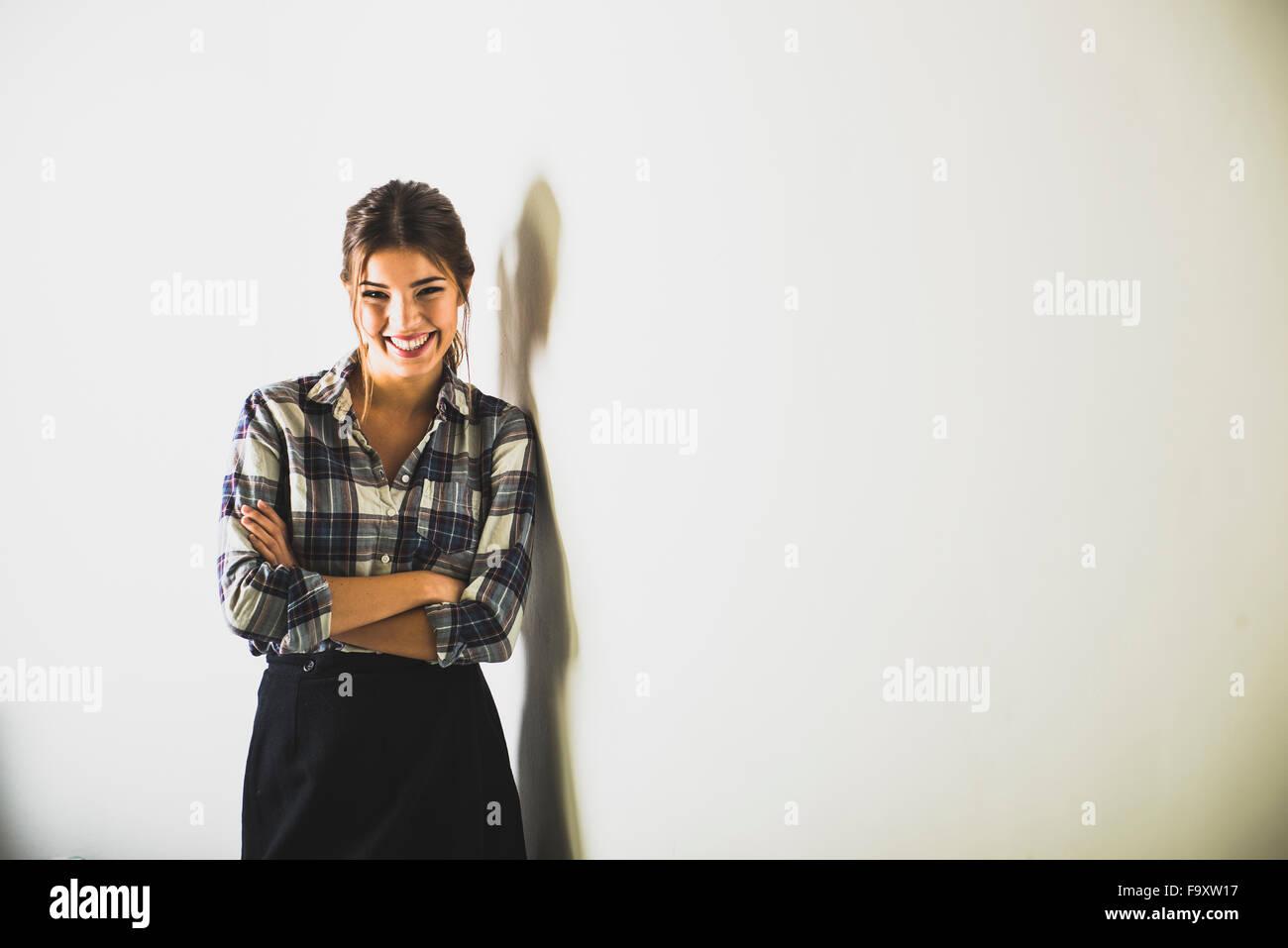 Lächelnde Brünette Frau, die an einer Wand stehend Stockbild