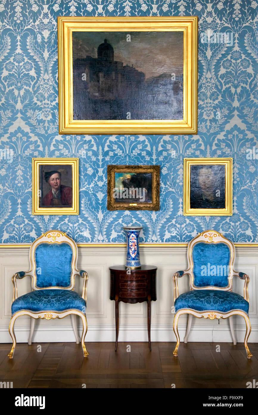 Blau, Gold und weiß gepolsterte Stühle und eine Wand aus Gemälden ...