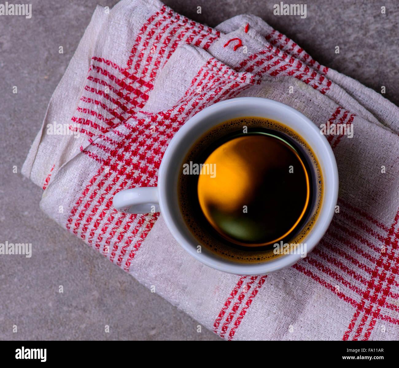 eine Tasse schwarzen Kaffee auf einer roten weißen Tischdecke Stockbild